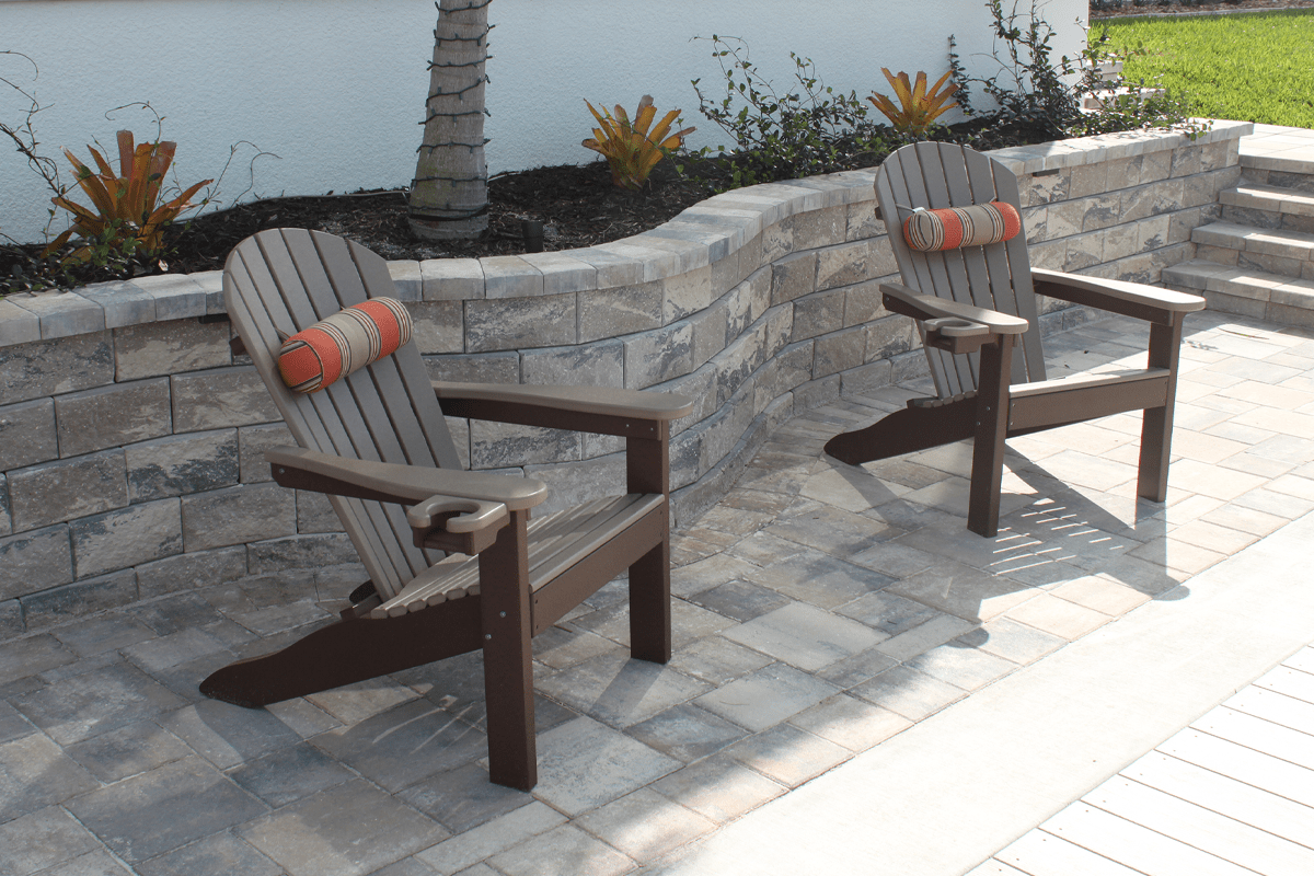 Wall paver collection with a paved floor and wooden beach chairs to relax in near a house